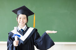 Graduation girl with showing gesture in classroom. Smiling graduation girl with showing gesture in classroom Royalty Free Stock Photography