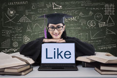 Graduation girl showing like on laptop screen. Asian graduate in graduation gown show like on laptop screen Royalty Free Stock Photography
