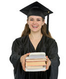 Graduation girl student giving stack of books. Isolated on white Royalty Free Stock Photo