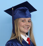 Graduation girl. A girl wearing a graduation outfit, against a blue background Stock Photography