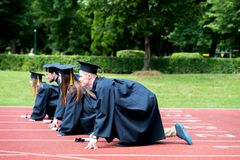 Graduation group of students celebrating on athletic track, prep royalty free stock photography