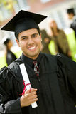 Graduation: Handsome Latino Student Graduate. Extensive series of recent student graduates after graduation, outside with friends.  Muti-ethnic group includes Stock Images