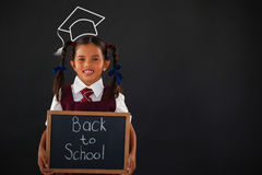 Composite image of graduation hat. Graduation hat  against portrait of schoolgirl holding slate with text against blackboard Stock Photos