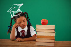 Composite image of graduation hat. Graduation hat  against unhappy schoolgirl looking at books stack and apple against chalkboard Royalty Free Stock Image