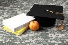 Graduation hat, apple and books Royalty Free Stock Photos