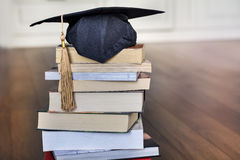 Graduation hat on books. Black graduation cap on pile of books royalty free stock photo