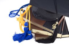 Graduation Hat Books and Cords. A black graduation hat with tassel and 2009 on a stack of books with blue and gold honors cords, isolated on white with copy stock photos