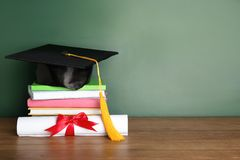 Graduation hat with books and diploma on table near chalkboard