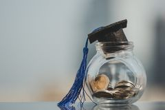 Graduation hat on coins money in the glass bottle on white background. stock images