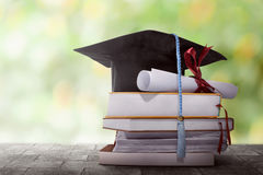 Graduation hat with degree paper on a stack of book royalty free stock images