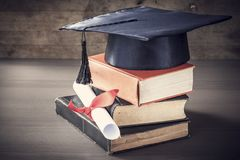 Graduation hat and diploma with book on table Stock Photography
