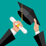 Graduation hat and diploma in hands of student Royalty Free Stock Images