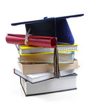 Graduation hat and diploma on stack of books Royalty Free Stock Photos