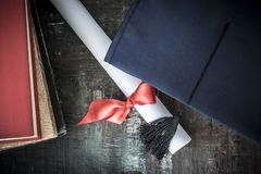 Graduation hat and diploma on table Royalty Free Stock Photography