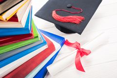 Graduation hat and diploma on white table stock photography