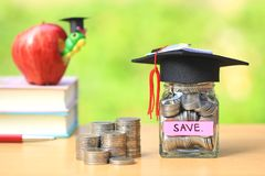 Graduation hat on the glass bottle and books on natural green background, Saving money for education concept stock photos