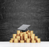 Graduation hat is laying on the coins pyramid. A concept of a high price for the university education. Chalkboard on the backgroun Royalty Free Stock Photos