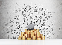 Graduation hat is laying on the coins pyramid. A concept of a high price for the university education. Stock Photo