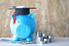 Graduation hat on piggy and tack of coins money on wooden backgr royalty free stock images