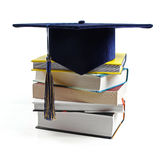 Graduation hat and stack of books isolated on white Royalty Free Stock Photo