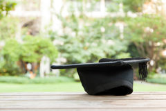 Graduation hat on vintage table with green nature background Royalty Free Stock Photography