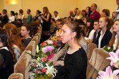 Graduation in high school. Graduates of the general education school celebrating the end of schooling and receiving diplomas.  In the assembly hall are children Stock Photo