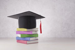 Graduation and intelligence concept. Abstract graduation hat and colorful book pile placed on concrete background. Graduation and intelligence concept. 3D Stock Photo
