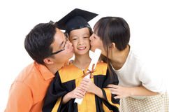 Graduation kid. Asian kindergarten child in graduation gown and mortarboard kissed by her parent during graduation stock photo