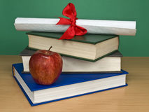 Graduation kit. A pile of books, an apple and a diploma stock images