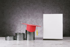 Graduation, knowlegde, financial growth and success concept. Silver coins with mortarboard and empty poster on concrete background. Graduation, knowledge Stock Photography