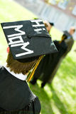 Graduation: Male Student with Message on Mortarboard. Extensive series of recent student graduates after graduation, outside with friends. Muti-ethnic group royalty free stock images