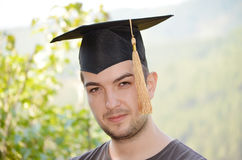 Graduation man portrait smiling and looking hap Royalty Free Stock Photography