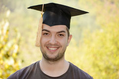 Graduation man portrait smiling and looking hap Stock Photo