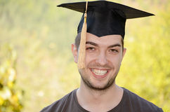 Graduation man portrait smiling and looking hap Royalty Free Stock Images