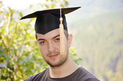 Graduation man portrait smiling and looking hap Stock Images
