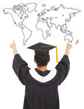 Graduation man wearing a mortarboard and point to world Royalty Free Stock Photos