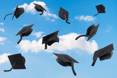 Graduation Mortar Boards. Thrown into a blue sky Royalty Free Stock Photos