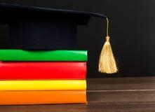 Graduation mortarboard on books Stock Photo