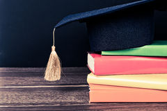 Graduation mortarboard on books Stock Photo