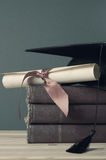 Graduation Mortarboard, Degree Scroll and Books - Faded Tones. A mortarboard and parchment diploma scroll tied with ribbon, on top of a pile of old books on a royalty free stock image