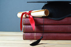 Graduation Mortarboard, Scroll and Books. Graduation mortarboard and scroll tied with red ribbon on top of a stack of old, worn books on a light wood table Royalty Free Stock Photos