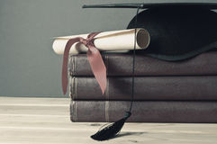 Graduation Mortarboard, Scroll and Books - Faded Tones Royalty Free Stock Photos