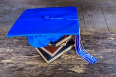 Graduation mortarboard on top of stack of books on abstract background stock photos