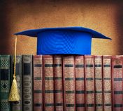 Graduation mortarboard on top of stack of books Royalty Free Stock Images