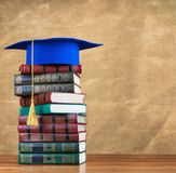 Graduation mortarboard on top of stack of books. On abstract background of wall Stock Photos