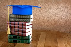 Graduation mortarboard on top of stack of books Stock Image