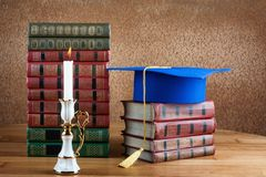 Graduation mortarboard on top of stack of books on wooden table royalty free stock image