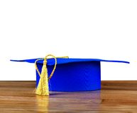 Graduation mortarboard on wooden table Royalty Free Stock Image