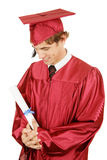 Graduation Pride. New graduate looks with pride at his diploma. Isolated on white stock images