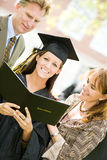 Graduation: Proud Daughter With Diploma and Parents. Extensive series of recent student graduates after graduation, outside with friends.  Muti-ethnic group Royalty Free Stock Photo